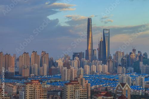 Plexiglas Shanghai Luftaufnahme der Skyline von Shanghai in der Abendsonne fotografiert aus Richtung Pudong bei teils bewölktem Himmel in China im November 2014