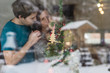 Happy young family with baby behind decorated Christmas tree at home