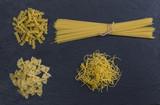 Different types of Italian pasta on dark stone plate - 184345280