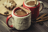 Traditional winter eggnog in decorative mugs with cinnamon/Traditional winter eggnog in decorative mugs with cinnamon on a dark background. Selective focus - 184350825