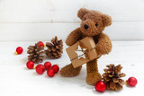 cute teddy bear with a Christmas gift, cones and red balls on a white painted wooden background, copy space - 184353655