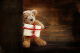cute little teddy bear half behind a wooden wall brings a Christmas present decorated with a red ball chain, dark rustic wood background with copy space - 184353682