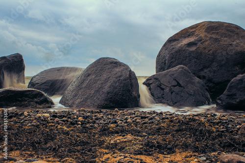 Tuinposter Bleke violet Steine am Strand mit Wellen und Gischt