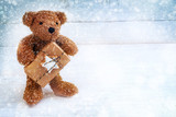 little teddy bear with a Christmas gift standing on a white blue painted wooden background in the snow, copy space - 184355011