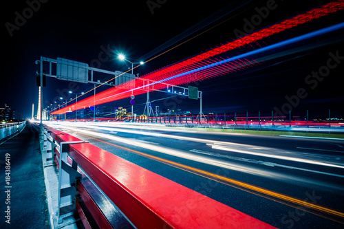 In de dag Tunnel light trails go though the bridge in the downtown district, china.