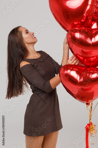 Young beautiful girl with red air balloons on a grey background Poster