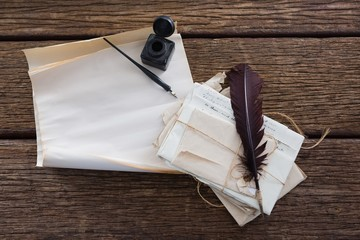 Quill feather, ink bottle, ink pen and legal documents on table