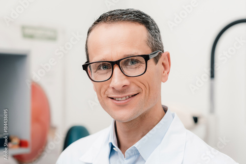 portrait of smiling doctor in eyeglasses looking at camera in clinic