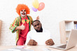 A man in a clown suit is standing beside a black man who sits at his desk.