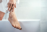 Well groomed woman's feet on bathtub edge