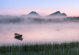 Fototapety Very peaceful summer night with wooden boat and fog in Lofoten, Norway