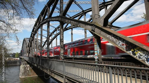 Plakat Passenger train passing by at an old iron bridge over the Main river in Frankfurt Main, Germany