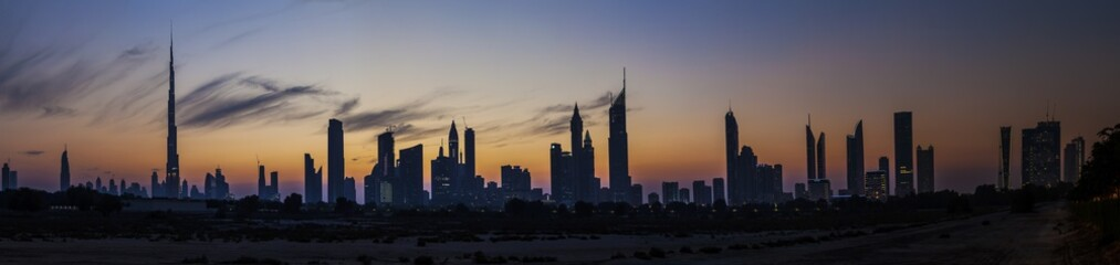 Panorama der Skyline von Dubai mit Silhouette der Wolkenkratzer im Gegenlicht fotografiert Abends bei klarem Himmel im November 2014
