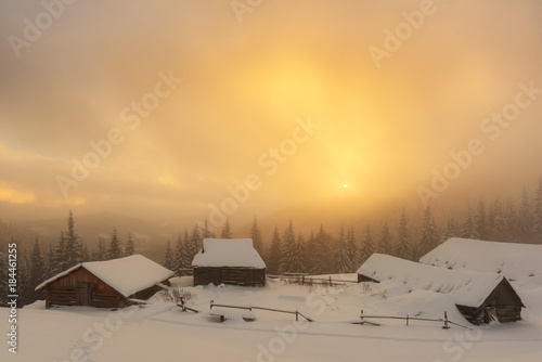 Fotobehang Winter Fantastic orange winter landscape in snowy mountains glowing by sunlight. Wooden house on a foreground. Christmas holiday concept. Carpathian mountain, Ukraine, Europe