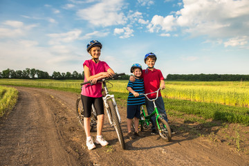 Sporty children in helmets with bikes