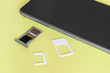 Adapters on a SIM card from larger to nano-sim with a SIM card in the slot near and a memory card with a phone on a yellow background, close up