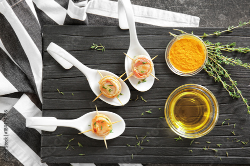Fotobehang Kruiden 2 Spoons with bacon wrapped scallops on wooden board