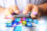 Apps browsing or development suggested by colorful icons in front a smartphone in programmer hands - 184495841