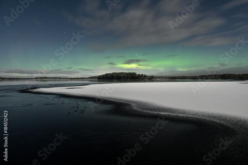 Fotobehang Noorderlicht Aurora Borealis aka northern lights seen behind partly iced lake at winter night in Kurjenrahka National Park, Finland