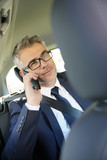 Businessman talking on phone in taxi cab - 184530223