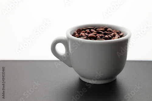 Keuken foto achterwand Koffiebonen Coffee beans in a cup/ Coffee beans in a cup, standing on a wooden table