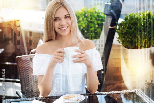 Wall mural Hot coffee. Beautiful jolly good kind woman smiling to the camera while relaxing and carrying cup