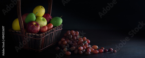 Fresh and withered fruits with Light in dark background / Still Life image and space for message.Fresh and withered fruits with Light in dark background