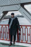 stylish middle aged man in coat with folded umbrella standing on bridge