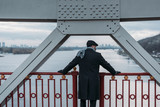 thoughtful adult man standing on bridge and looking at river