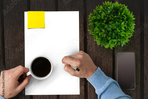 Wall mural Man drinking coffee on a piece of paper