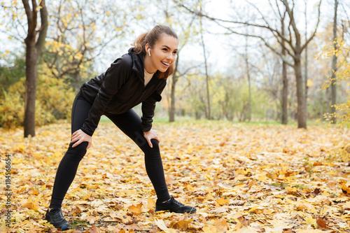 Portrait of a smiling fitness girl in earphones resting