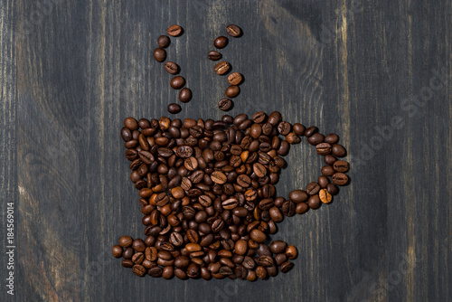 cup of coffee beans on a wooden background, concept photo