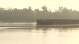 Long Metal Barge Floats Along The Dnipro With Trees in the Background - 184571812