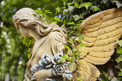 A fragment of ancient sculpture angel in a golden glow in the old cemetery. - 184575207