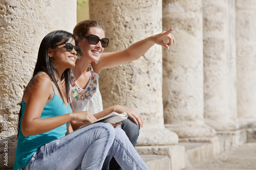 Smiling women sitting on colonnade