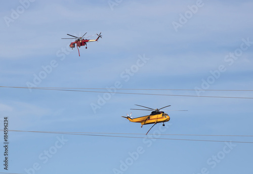 Red and Yellow Fire Helicopters Pass Each Other in Fire Fight