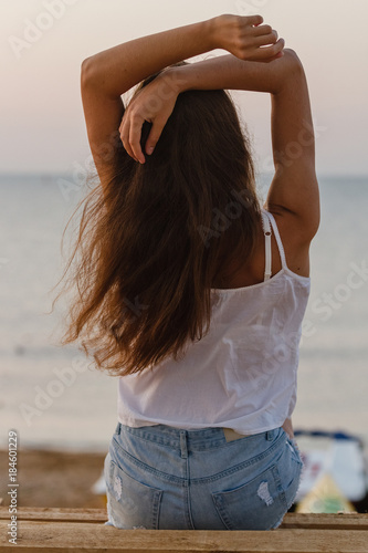young woman with curly hair sittin on the morning beach Poster