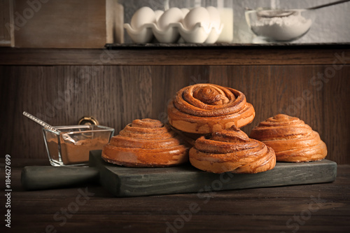Fotobehang Kruiden 2 Wooden board with tasty cinnamon buns on table