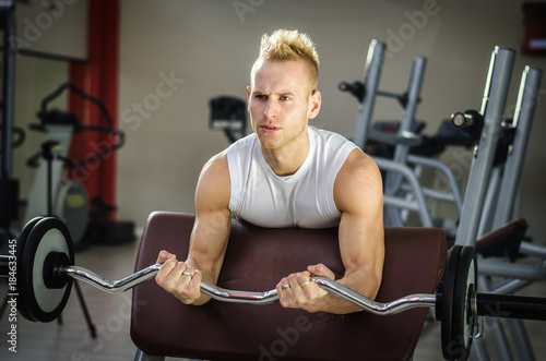 Póster Handsome young man training biceps lifting barbell on bench in a gym, looking st