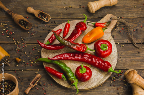 Tuinposter Hot chili peppers variety of peppers on a wooden background.