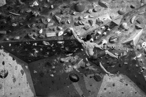 Wall mural Active man with fit muscular body doing gym climbing.