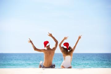 Happy couple in Santa's hats at tropical beach
