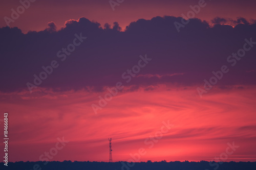 Fotobehang Aubergine tower on the horizon against the background of the setting sun in the color of the year 2018 ultra violet