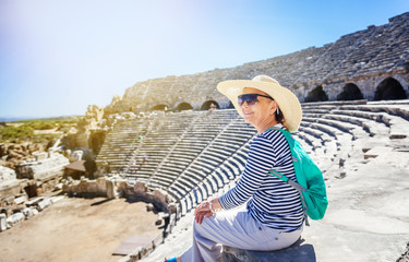 Mature beautiful woman traveler, sits on the steps of the amphitheater in admiring the view. Travel to Greece and Turkey, the monuments of ancient architecture, active seniors