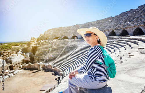 Foto Murales Mature beautiful woman traveler, sits on the steps of the amphitheater in admiring the view. Travel to Greece and Turkey, the monuments of ancient architecture, active seniors