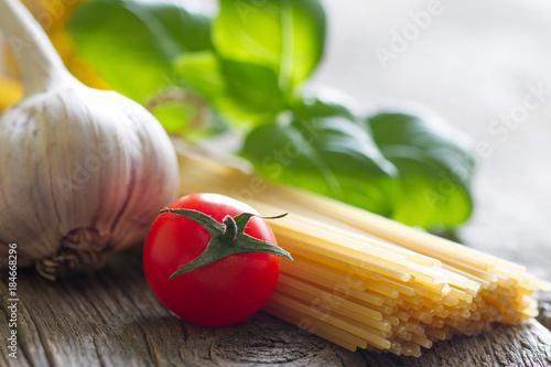 Basil tomato and garlic italian food still life with pasta on retro planks