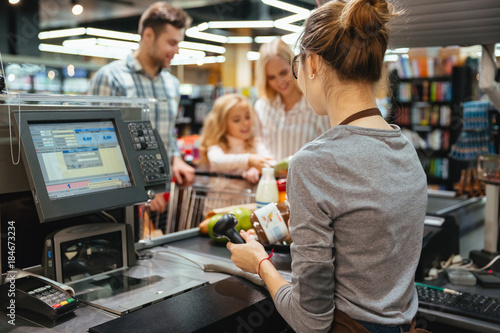 Beautiful family standing at the cash counter