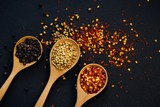 Various spices in wooden spoon on dark black background, top view - 184700027