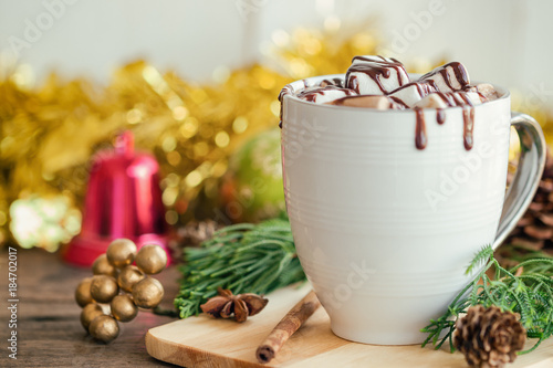 Foto op Canvas Chocolade Hot chocolate in white cup topping with marshmallow and dark chocolate sauce on wood table in side view, copy space with Christmas theme decoration background. Concept to present Xmas drink.
