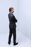 serious businessman standing in corner - 184711438